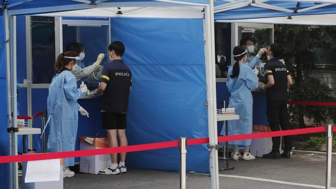 Petugas medis mengambil sampel dari petugas polisi selama pengujian COVID-19 di Badan Kepolisian Metropolitan Seoul di Seoul, Korea Selatan, Rabu, (19/8/2020). (AP Photo / Ahn Young-joon)