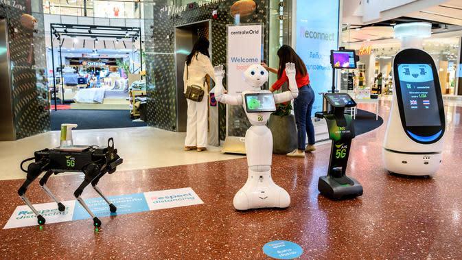 Robot 5G menyambut pengunjung yang mendatangi pusat perbelanjaan di Bangkok, Thailand, Kamis (4/6/2020). Saat ini Thailand sedang dalam proses membuka kembali pusat perbelanjaan setelah sebelumnya ditutup selama dua bulan karena pandemi Covid-19. (Mladen ANTONOV / AFP)