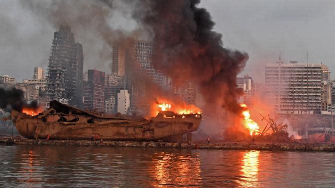 Sebuah kapal besar yang terbakar setelah ledakan besar di pelabuhan Kota Beirut, Lebanon (5/8/2020). Kuatnya ledakan di Beirut sampai kapal tersebut terangkat ke Daratan dan hancur. (AFP Photo)
