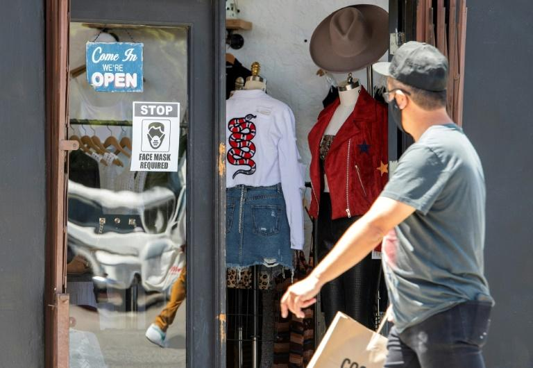 A man wearing a mask walks by a store requiring shoppers wear masks during the coronavirus pandemic, on May 27, 2020, in Los Angeles, California