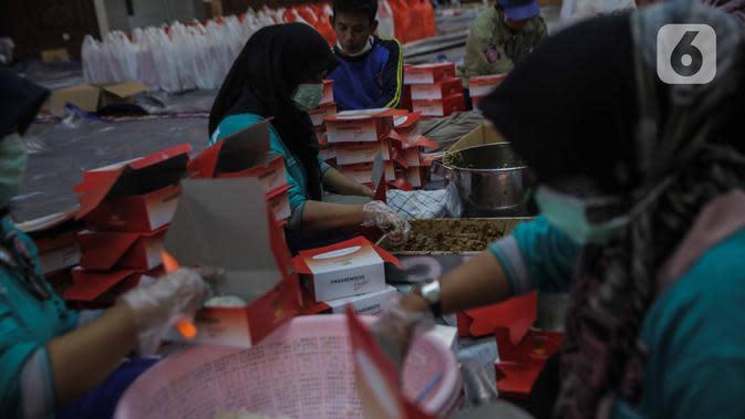 Petugas Taruna Siaga Bencana menyiapkan nasi kotak di Dapur Umum Kementerian Sosial Peduli Dampak Covid-19 di Kompleks Gedung Konvensi TMP Nasional-Utama, Kalibata, Jakarta, Rabu (8/4/2020). Paket nasi itu didistribusikan ke warga DKI yang terdampak pandemi Covid-19. (Liputan6.com/Faizal Fanani)