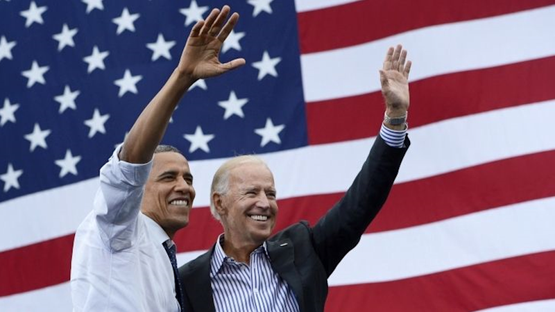 Barack Obama and Joe Biden wave while standing in front of a US flag.