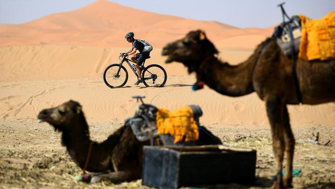 Pebalap mengendarai sepeda saat sesi latihan balap sepeda gunung Titan Gurun 2019 di sekitar Kota Merzouga, Maroko, Sabtu (27/4/2019). Trek Titan Gurun 2019 sepanjang 640 km menghubungkan antara Merzouga dan Maadid. (Franck Fife / AFP)
