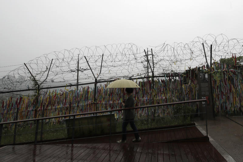 A woman walks near the wire fences decorated with ribbons written with messages wishing for the reunification of the two Koreas at the Imjingak Pavilion in Paju, South Korea, Wednesday, June 24, 2020. North Korea said Wednesday leader Kim Jong Un suspended a planned military retaliation against South Korea, possibly slowing the pressure campaign it has waged against its rival amid stalled nuclear negotiations with the Trump administration. (AP Photo/Lee Jin-man)