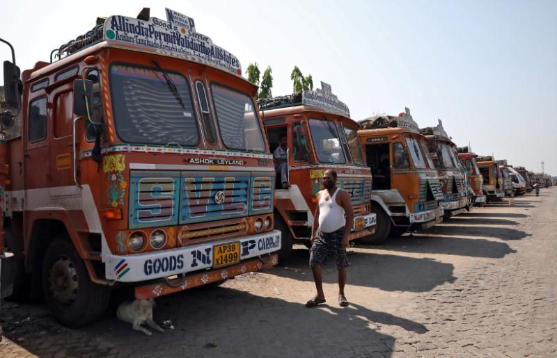A man walks past parked supply trucks at a yard during a 21-day nationwide lockdown to limit the spreading of coronavirus disease (COVID-19), on the outskirts of Kolkata