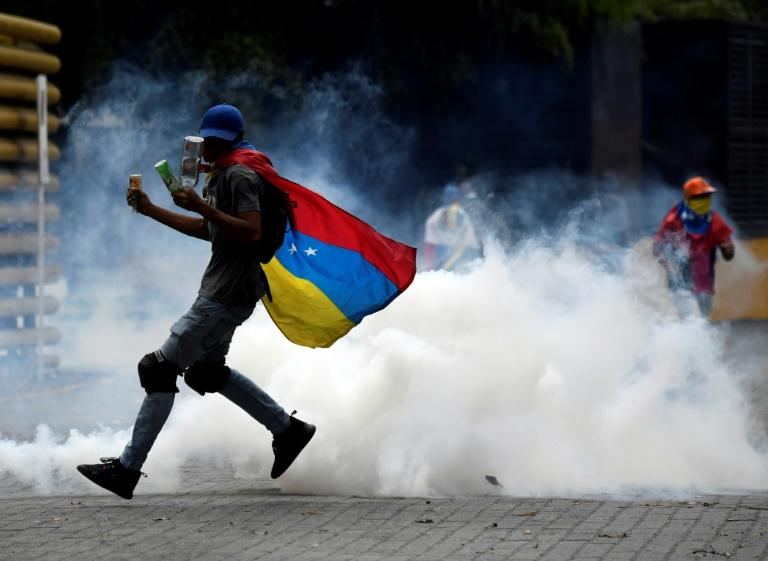 A supporter of Venezuelan opposition leader Juan Guaido shoots back a tear gas canister shot by security forces during clashes on March 10, 2020