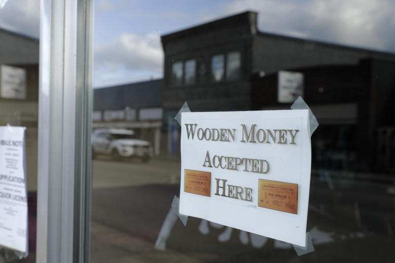 In this May 21, 2020 photo, a sign on a business in Tenino, Wash. says they will be accepting wooden money. In an effort to help residents and local merchants alike get through the economic fallout of the coronavirus pandemic, the small town has issued wooden currency for residents to spend at local businesses, decades after it created a similar program during the Great Depression. (AP Photo/Ted S. Warren)
