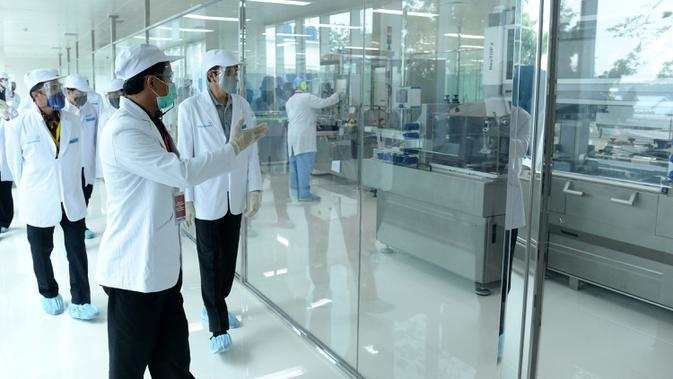 Presiden Joko Widodo atau Jokowi (kanan) meninjau fasilitas produksi dan pengemasan di PT Bio Farma, Bandung, Jawa Barat, Selasa (11/8/2020). Jokowi menggunakan pakaian lengkap penelitian untuk melihat Laboratorium Bio Farma. (Foto: Biro Pers Kepresidenan)