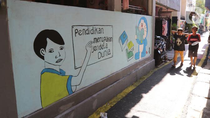 Anak-anak melintasi mural di Kampung Budaya Kawasan Jakarta Barat, Selasa (19/11/2019). Penataan dilakukan mulai daari pembenahan jalan, pembuatan resapan air, bangku, mural, hingga ubin pemandu untuk penyandang disabilitas dengan anggaran mencapai Rp2.5 miliar. (Liputan6.com/Herman Zakharia)