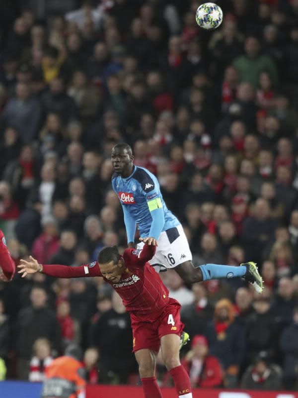 Bek Napoli, Kalidou Koulibaly berebut bola udara dengan bek Liverpool, Virgil van Dijk pada pertandingan Grup E Liga Champions di stadion Anfield, Inggris (27/11/2019). Liverpool bermain imbang 1-1 atas Napoli. (AP Photo/Jon Super)