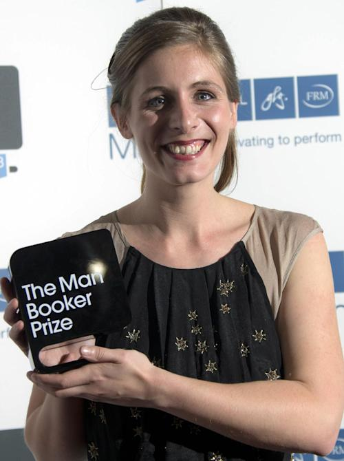 New Zealand author Eleanor Catton poses after being announced the winner of the Man Booker Prize for Fiction, holding her prize for the photographers, in central London, Tuesday Oct. 15, 2013. Catton won the 50,000 pounds ($80,000) prize with her book 'The Luminaries'. (Photo by Joel Ryan/Invision/AP)