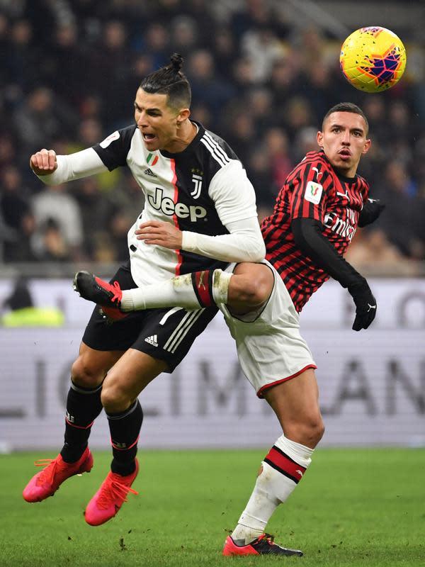 Pemain Juventus Cristiano Ronaldo (kiri) berebut bola dengan pemain AC Milan Ismael Bennacer pada pertandingan Coppa Italia di Stadion San Siro, Milan, Italia, Kamis (13/2/2020). Pertandingan berakhir 1-1. (Massimo Paolone/LaPresse via AP)
