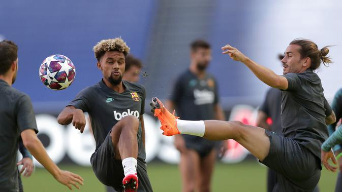 Penyerang Barcelona, Antoine Griezmann berebut bola dengan Konrad de la Fuente selama sesi latihan di stadion Da Luz, Lisbon, Portugal (13/8/2020). Barcelona akan bertanding melawan Bayern Munchen pada perempat final Liga Champions di Estadio da Luz. (Rafael Marchante/Pool via AP)
