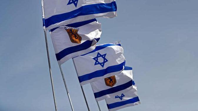 Bendera Israel berkibar di dekat Gerbang Jaffa di Kota Tua Yerusalem (20/3). Gerbang Jaffa adalah sebuah portal yang dibuat dari batu yang berada dalam deret tembok bersejarah Kota Lama Yerusalem. (AFP Photo/Thomas Coex)