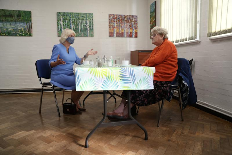 Britain's Camilla, Duchess of Cornwall, in her role as President, Royal Voluntary Service, wears a facemask as she meets Doris Winfield, 86, during her visit to the Royal Voluntary Service Mill End lunch club in Rickmansworth, Hertfordshire on October 8, 2020, to meet volunteers who have overcome recent challenges posed by the novel coronavirus COVID-19 pandemic to reinstate the much-needed lunch sessions. (Photo by Andrew Matthews / POOL / AFP) (Photo by ANDREW MATTHEWS/POOL/AFP via Getty Images)
