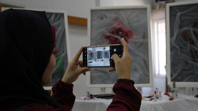 Seorang perempuan memotret karya seni di pameran seniman Palestina Kholoud al-Dasooqi di Gaza City, 11 Agustus 2020. Seniman asal Kota Khan Younis di Jalur Gaza itu menggelar pameran selama dua hari untuk mengungkap kekerasan terhadap perempuan melalui puluhan lukisan. (Xinhua/Rizek Abdeljawad)