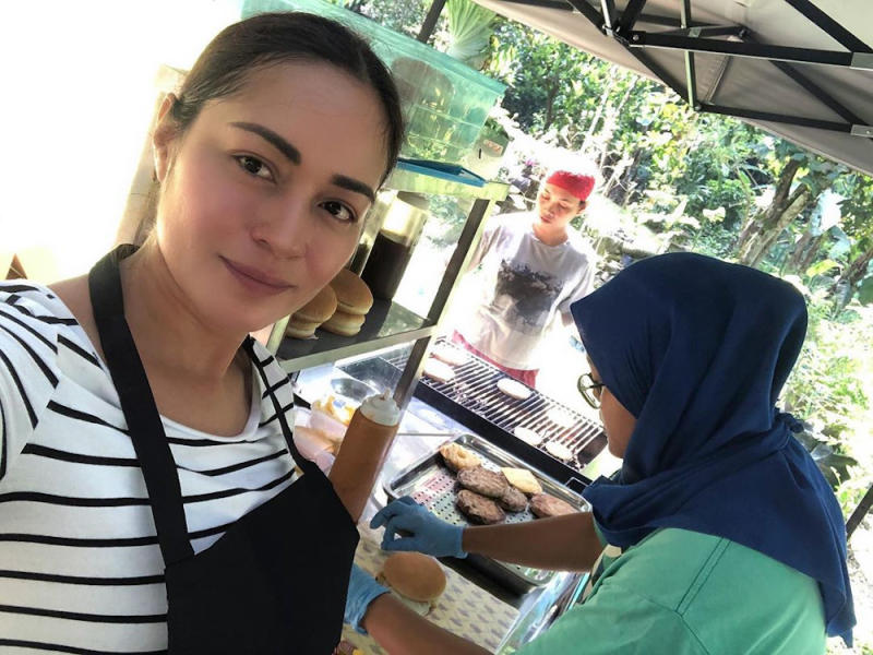 The 'Pontianak Harum Sundal Malam' star flipping burgers with a staff member in April. — Picture from Instagram/Maya Karin