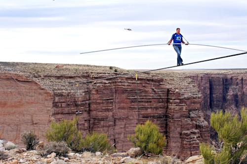 Aerialist Nik Wallenda near the end of his quarter mile walk over the Little Colorado River Gorge in northeastern Arizona on Sunday, June 23, 2013. The daredevil successfully traversed the tightrope strung 1,500 feet above the chasm near the Grand Canyon in just more than 22 minutes, pausing and crouching twice as winds whipped around him and the cable swayed. (AP Photos/Discovery Channel, Tiffany Brown)
