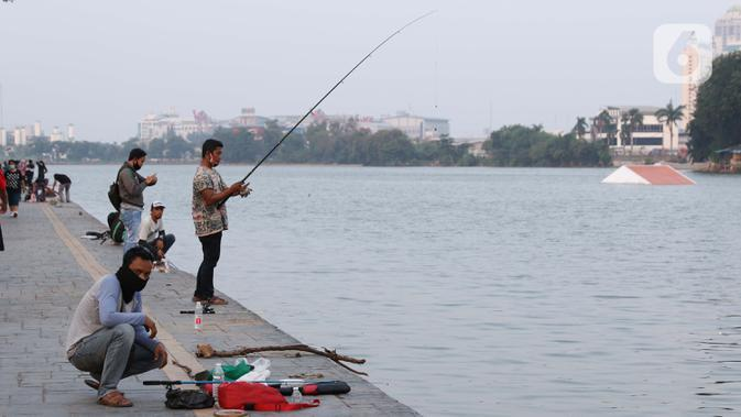 Warga memancing di area pedestrian Danau Sunter, Jakarta, Sabtu (27/6/2020). Beragam aktivitas dilakukan warga sambil menikmati waktu sore di area Danau Sunter, Jakarta. (Liputan6.com/Helmi Fithriansyah)