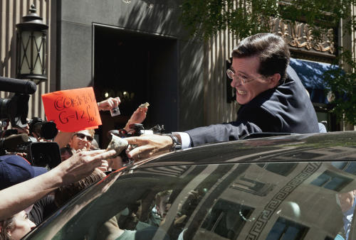 Comedian Stephen Colbert grabs cash money from a supporter as he climbs into a vehicle to depart the Federal Election Commission in Washington, Thursday, June 30, 2011, after the FEC granted his request to form a Political Action Committee. (AP Photo/Cliff Owen)