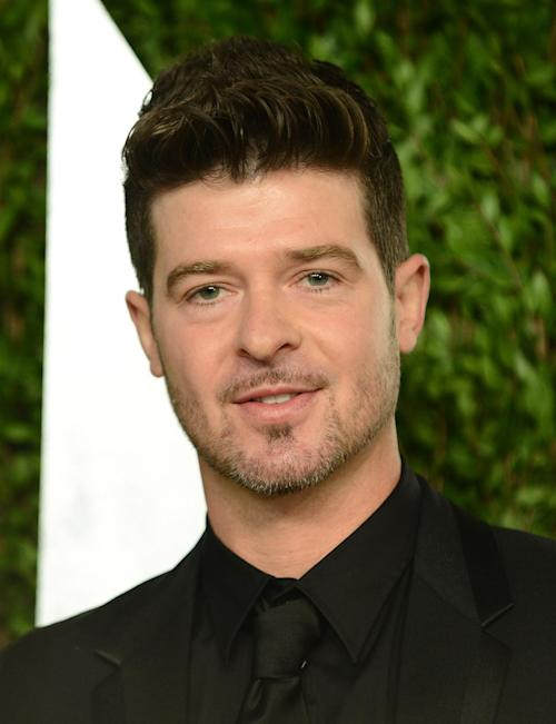 "FILE - In this Feb. 24, 2013 file photo, Robin Thicke arrives at the 2013 Vanity Fair Oscars Viewing and After Party at the Sunset Plaza Hotel in West Hollywood, Calif. Thicke originally didn't plan to release the unrated version of his music video for the song ""Blurred Lines,"" which features nude models prowling around him and rappers Pharrell and T.I. (Photo by Jordan Strauss/Invision/AP, File)"