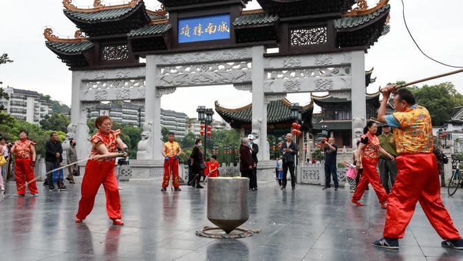 Anggota Klub Gasing Kylin Guiyang memainkan sebuah gasing raksasa di Lapangan Jiaxiulou di Guiyang, Provinsi Guizhou, China barat daya, (15/5/2020). Sekitar 38 anggota klub tersebut menampilkan atraksi memainkan gasing seberat 243,08 kilogram di Guiyang pada Jumat (15/5). (Xinhua/Ou Dongqu)