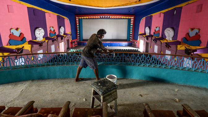 Pekerja membersihkan ruang bioskop sebagai persiapan kemungkinan pembukaan kembali setelah pelonggaran pembatasan Covid-19, di Chennai, Sabtu (3/10/2020). Kementerian Kesehatan India melaporkan pada Sabtu (3/10) total kematian di India akibat virus corona naik menjadi 100,842. (Arun SANKAR/AFP)