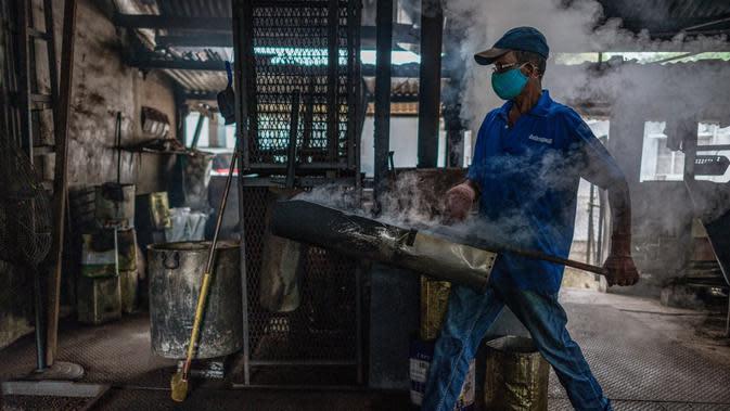 Pekerja membawa biji kopi panggang di Pabrik Kopi Antong, Taiping, Perak, Malaysia, 28 September 2020. Pabrik Kopi Antong menggunakan mesin antik dan metode pemanggangan tradisional untuk menghasilkan bubuk sarat kafein yang terkenal selama 87 tahun. (Mohd RASFAN/AFP)