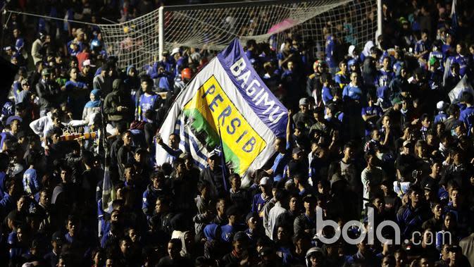 Aksi Bobotoh mengibarkan bendera dengan logo klub Persib Bandung pada Launching Jersey dan tim di Stadion Siliwangi, Bandung, Minggu (2/4/2017). Jersey baru akan digunakan untuk mengarungi Liga 1 Indonesia. (Bola.com/Nicklas Hanoatubun)