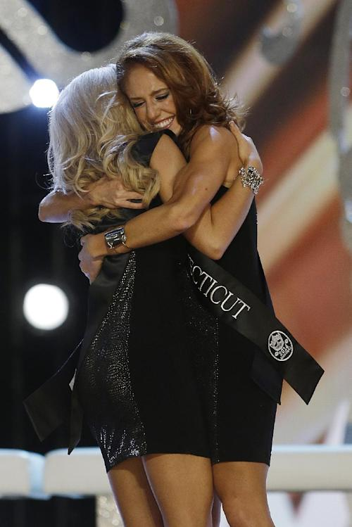 Miss Connecticut Kaitlyn Tarpey, right, hugs Miss Georgia Carly Mathis during the Miss America 2014 pageant, Sunday, Sept. 15, 2013, in Atlantic City, N.J. (AP Photo/Mel Evans)