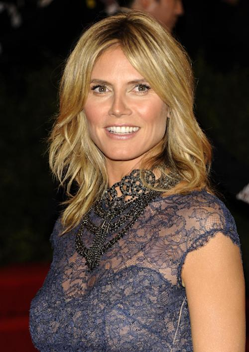 """FILE - This May 7, 2012 file photo shows model and TV host Heidi Klum arriving at the Metropolitan Museum of Art Costume Institute gala benefit in New York. Klum is denying that she had an affair with her bodyguard while married to pop singer Seal. But now, having split from Seal, she says she is seeing the bodyguard. On Wednesday's edition of the Katie Couric talk show, Klum said she """"never looked at another man"""" while she and Seal were together. But more recently, she and the family's bodyguard of four years have gotten to know each other """"from a completely different side."""" (AP Photo/Evan Agostini, file)"""