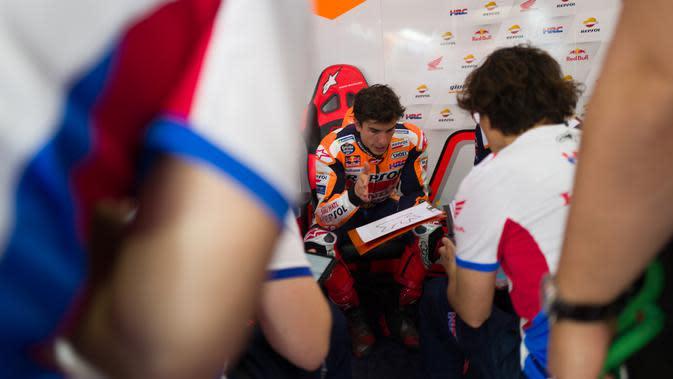 Marc Marquez tampak sangat serius berbincang dengan kru tim Repsol Honda pada tes pramusim MotoGP 2020 di Sirkuit Losail, Qatar. (Twitter/Repsol Honda)
