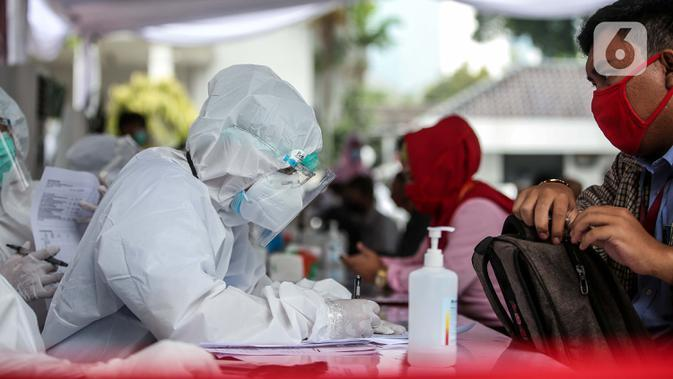 Petugas kesehatan mendata pegawai KPU dan Wartawan saat mengikuti swab test dan tes diagnostik cepat (rapid test) COVID-19 secara massal di Gedung KPU, Jakarta, Selasa (4/8/2020). (merdeka.com/Faizal Fanani)