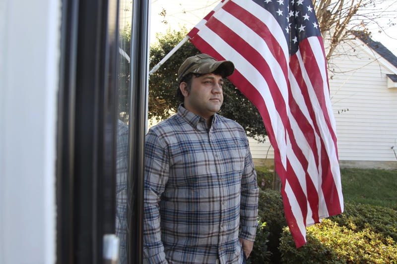 In this Monday, Dec. 16, 2019, photo, Zia Ghafoori stands beside an American flag hanging at his Charlotte, N.C., home. The Afghan interpreter spent 14 years working alongside U.S. Special Forces. He received a Special Immigrant Visa in 2014 and is working toward becoming a U.S. citizen. (AP Photo/ Sarah Blake Morgan)