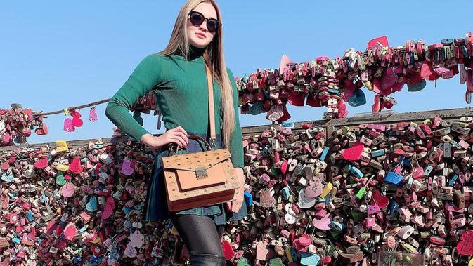Saat traveling di Namsan Tower, Korea Selatan, gaya Nella Kharisma saat OOTD menjadi sorotan publik. Ia tampil dengan simpel dan elegan memakai kaus warna hijau. Ditambah lagi kacamata hitam yang ia pakai semakin membuatnya terlihat cantik. (Liputan6.com/IG/@nellakharisma)