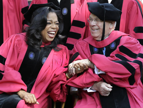 Oprah Winfrey clasps hands with Boston Mayor Thomas Menino prior to their receiving honorary degrees from Harvard University at commencement ceremonies in Cambridge, Mass., Thursday, May 30, 2013. (AP Photo/Elise Amendola)