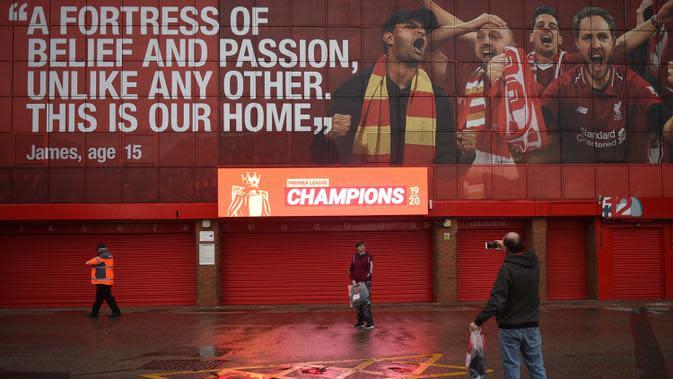 Seorang penggemar Liverpool berfoto di bawah layar digital baru merayakan Liverpool menyegel gelar Liga Premier malam sebelumnya, di luar stadion Anfield di Liverpool, Inggris (26/6/2020). (AFP Photo/Oli Scarff)