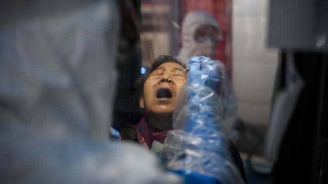 Seorang wanita mendapat test swab virus corona COVID-19 di luar Rumah Sakit Yangji, Seoul, Korea Selatan, 17 Maret 2020. Jumlah pasien virus corona COVID-19 di Korea Selatan mencapai 8.799 kasus dengan 102 meninggal. (Photo by Ed JONES/AFP)