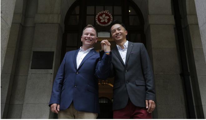 Angus Leung, with husband Scott Adams, won his legal battle last year. Photo: AP