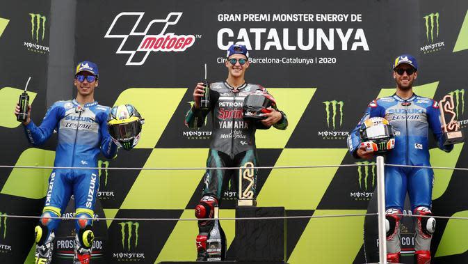 Alex Rins (paling kanan) saat finis ketiga pada balapan MotoGP Catalunya, 27 September 2020. Sementara rekan setimnya, Joan Mir (paling kiri) finis kedua. (AP Photo/Joan Monfort)