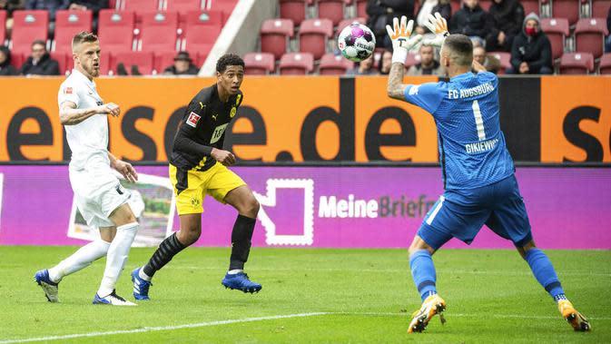Kiper Augsburg, Rafal Gikiewicz, menangkap bola saat melawan Borussia Dortmund pada laga Bundesliga, Minggu (27/9/2020). Augsburg menang dengan skor 2-0. (Matthias Balk/dpa via AP)