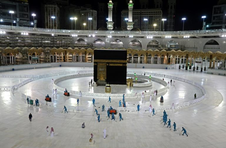 Sanitation workers disinfect the area around the Kaaba in Mecca's Grand Mosque, emptied of the usual hordes of foreign pilgrims by coronavirus restrictions introduced by the Saudi authorities in March