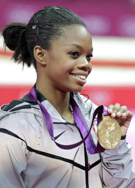 FILE - This Aug. 2, 2012 file photo shows U.S. gymnast Gabrielle Douglas displaying her gold medal during the artistic gymnastics women's individual all-around competition at the 2012 Summer Olympics in London. Douglas became the first African American woman to win Olympic gold in the individual all-around. The feat was joyous, but some on social media bemoaned that her hair wasn't perfect.  (AP Photo/Gregory Bull, File)