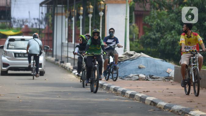 Pengunjung menaiki sepeda di Taman Mini Indonesia Indah, Jakarta, Kamis (20/8/2020). Warga memanfaatkan momen libur panjang Tahun Baru islam 1442 H ke tempat rekreasi yang dekat karena masih situasi pandemi Corona (COVID-19) dengan menjaga protokol kesehatan. (merdeka.com/Imam Buhori)