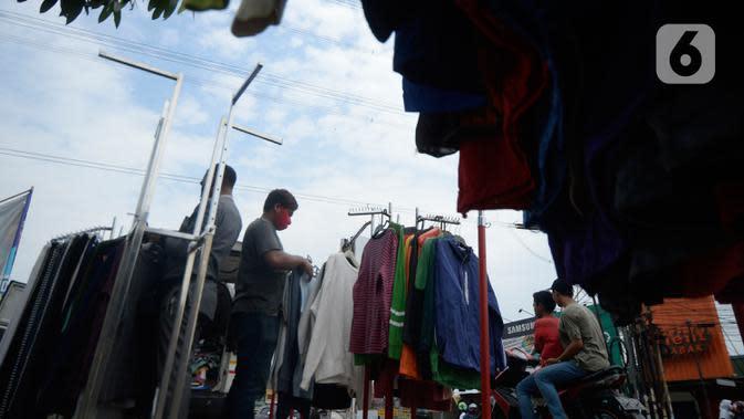 Pembeli sedang memilih baju seken (baju bekas) impor di pingir jalan wilayah Pamulang, Tangerang Selatan, Banten, Senin (29/9/2020). Pada saat pandemi baju bekas impor masih diminati masyarakat karena murah harganya. (merdeka.com/Dwi Narwoko)