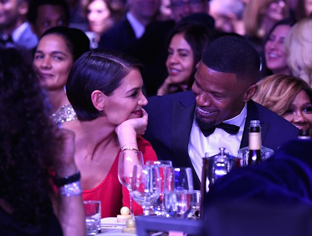 Katie Holmes and Jamie Foxx smile at each other at a pre-Grammy Awards event on Saturday night. (Kevin Mazur via Getty Images)