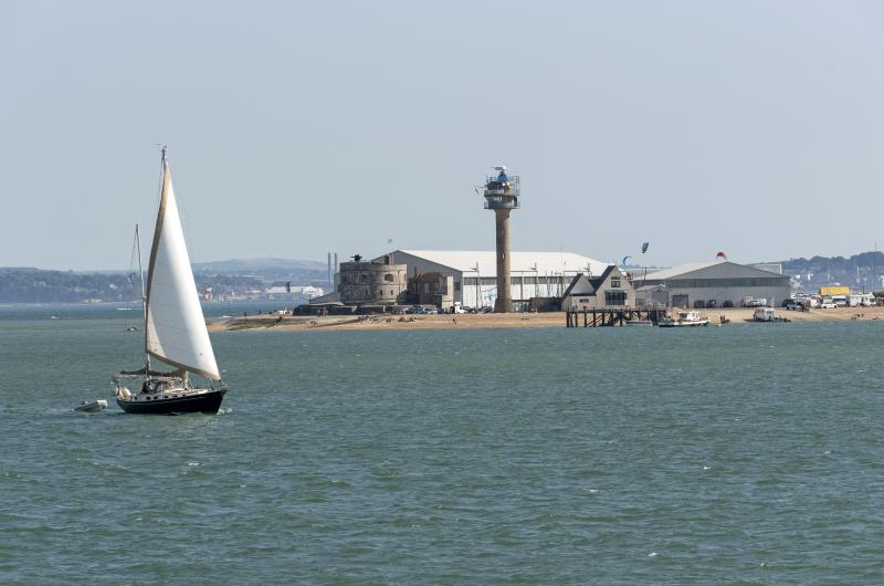 Sailing boat passing Calshot Activities center on the shores of the Solent, Calshot Spit, Southampton, England UK. (Photo by: Education Images/Universal Images Group via Getty Images)