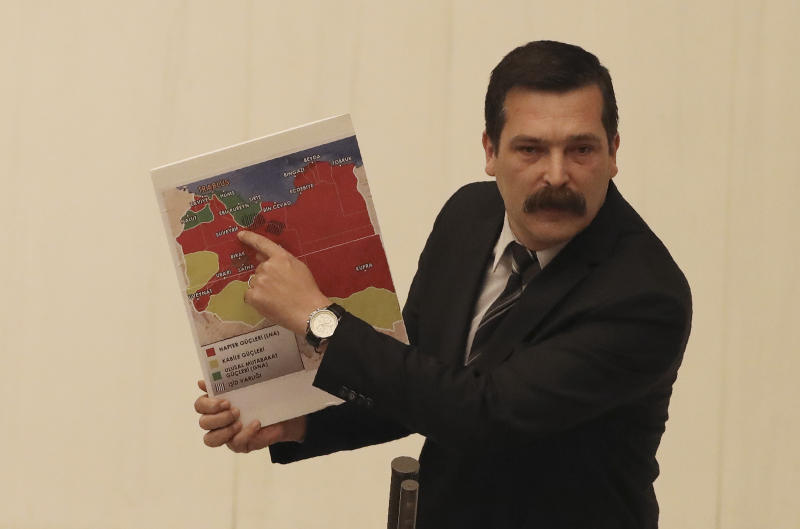 Erkan Bas, a lawmaker of the opposition Workers' Party, shows a map of divided Libya before Turkey's parliament authorized the deployment of troops to Libya to support the U.N.-backed government in Tripoli battle forces loyal to a rival government that is seeking to capture the capital, in Ankara, Turkey, Thursday, Jan. 2, 2020. Turkish lawmakers voted 325-184 at an emergency session in favor of a one-year mandate allowing the government to dispatch troops amid concerns that Turkish forces could aggravate the conflict in Libya and destabilize the region.(AP Photo/Burhan Ozbilici)