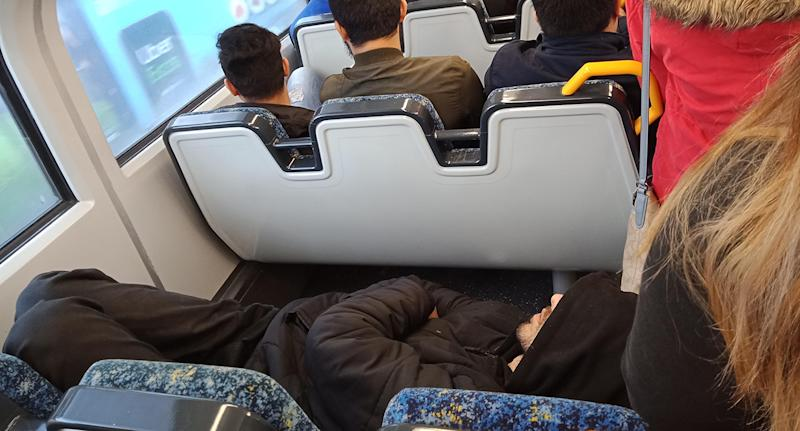 A man wearing all black, laying across three train seats on a crowded Sydney train.