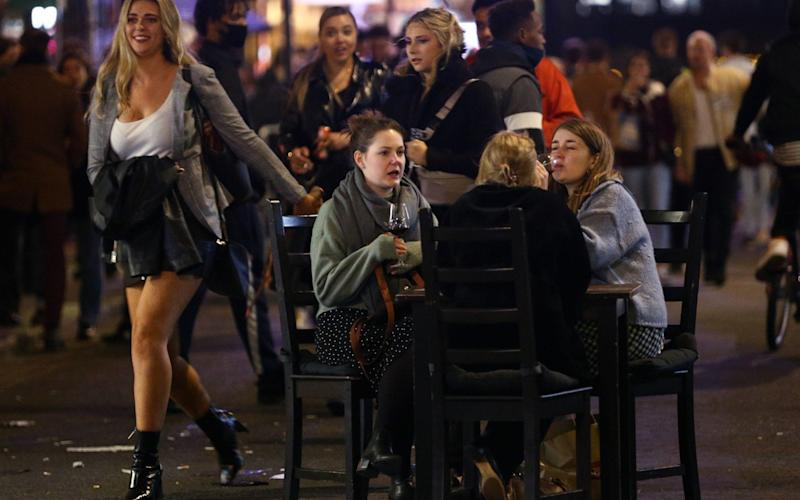 Revellers in Soho, London, finish their drinks before closing time at 10pm on Saturday - PA/Yui Mok